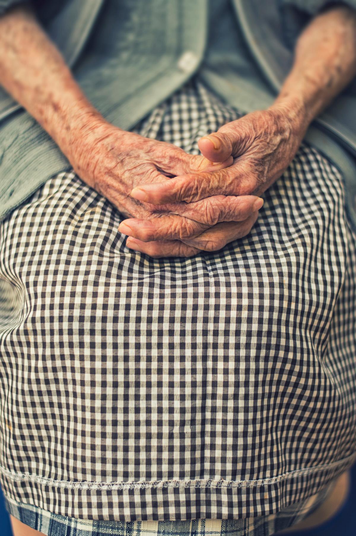 donna anziana con le mani incrociate